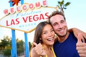 stock photo of las vegas casino  - Las vegas couple happy and excited at welcome to fabulous Las Vegas sign billboard at the strip - JPG
