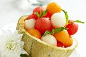 stock photo of cantaloupe  - Fruit salad with melon and watermelon balls in cantaloupe bowl