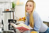 Teenager Girl Reading Book In Kitchen