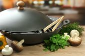 stock photo of chinese wok  - Black wok pan and vegetables on kitchen wooden table - JPG