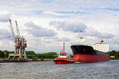 picture of towing  - Tugboat towing a large ship in port Gdansk - JPG