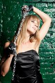image of sado-masochism  - beautiful woman with an steel chain on the background wall - JPG