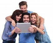 image of palm-reading  - excited group of friends reading surprising stuff on their tablet pad computer on white background - JPG