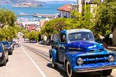 SAN FRANCISCO - APRIL 20, 2031: Vintage car on Hyde street over cable-car rail and Alacatraz island,