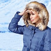 Woman looking away, wearing warm stylish blue coat with furry hood, wintertime fashion, cold weather, winter holidays concept poster