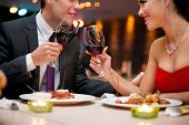 stock photo of diners  - hands of couple toasting their wine glasses over a restaurant table during a romantic dinner - JPG