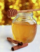 stock photo of cinnamon  - Honey with wood stick and cinnamon sticks - JPG