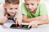 Two little smiling child boy brothers playing games or surfing internet on digital tablet computer