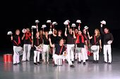 Orchestra drummers in costumes with hats raised on drumsticks, 14 people