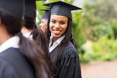 image of graduation  - pretty african university graduate looking back at graduation ceremony - JPG