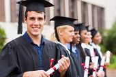 stock photo of graduation gown  - portrait of group cheerful college graduates at graduation - JPG