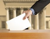 stock photo of ballot-paper  - Hand putting a voting ballot in a slot of box - JPG
