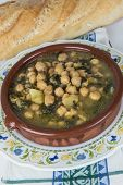 stock photo of bengal-gram  - Stew of chickpeas and spinach with cod on a table with a tablecloth - JPG