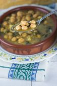 foto of bengal-gram  - Stew of chickpeas and spinach with cod on a table with a tablecloth - JPG