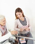 Happy senior woman playing cards with smiling granddaughter at home