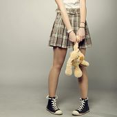 stock photo of splayed  - teenager girl in shitr with toy teddy bear - JPG