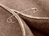 sepia toned clothing fragment with safety pin