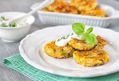 foto of patty-cake  - Healthy vegetarian cabbage patties with carrot onion and green against the backdrop of sour cream sauce with herbs - JPG