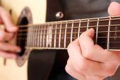 stock photo of close-up  - Close up of guitarist hand playing acoustic guitar - JPG