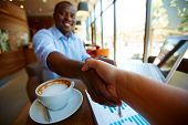 stock photo of latte  - Image of cup of latte and business document and handshaking of business partners in cafe - JPG