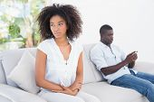 stock photo of not talking  - Attractive couple not talking on the couch at home in the living room - JPG