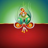 picture of rakhi  - Beautiful peacock feather and pearls decorated rakhi on green and red background for Raksha Bandhan celebrations - JPG