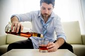 picture of alcohol abuse  - caucasian businessman alcoholic wearing a blue work shirt and tie drunk and drinking Scotch or Whiskey sitting on a sofa at home after a long day or week of work on a white background - JPG
