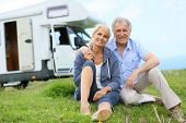 stock photo of recreational vehicle  - Happy senior couple sitting in grass - JPG