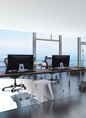 stock photo of movable  - Modern waterfront office overlooking the sea with several computer workstations on movable wheeled office tables in a bright airy room with a glass view window or wall - JPG