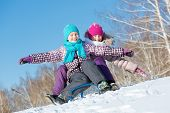 picture of sled  - Two cute girls riding sled and having fun - JPG