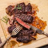 stock photo of ribeye steak  - Grilled Ribeye Steak with with knife and fork on meat cutting board on wooden background - JPG