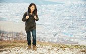 stock photo of recreation  - Traveler young smiling woman with backpack walking in highlands over the city - JPG