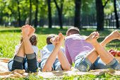 image of barefoot  - Young happy family lying in park barefoot - JPG
