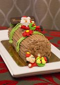image of yule  - Traditional Christmas Yule Log cake decorated with santa bear and fiower mazipan.