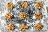 image of baked raisin cookies  - uncooked oatmeal cookies with raisins on baking tray - JPG