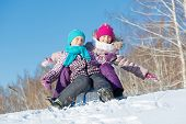 foto of sled  - Two cute girls riding sled and having fun - JPG