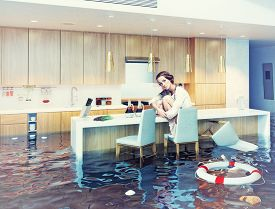 stock photo of combinations  - beautiful woman sitting on a chair in flooded kitchen interior - JPG