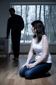 stock photo of kneeling  - Victim of domestic violence kneeling on the floor - JPG