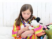 foto of teddy  - a sick little girl playing with her teddy in her bed - JPG