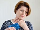 pic of throat  - Adult woman with a sore throat on a light background - JPG