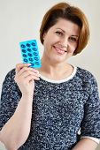picture of blisters  - Adult woman holding a blister pack of a pills - JPG