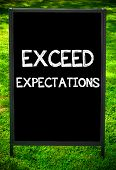 image of expectations  - EXCEED EXPECTATIONS message on sidewalk blackboard sign against green grass background - JPG