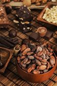 stock photo of cocoa beans  - Cocoa beans and chocolate assortment on table - JPG