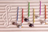 foto of compose  - Music at the seaside concept with an artistic arrangement of music notes formed from pebbles and colorful paintbrushes on a background score composed of alternating lines of golden sand - JPG