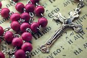stock photo of prayer  - Catholic rosary pink lie in the Bible or prayer book - JPG