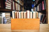 picture of wooden crate  - Books in wooden crate on bookshelves background - JPG