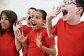 stock photo of drama  - Group Of Children Enjoying Drama Class Together - JPG
