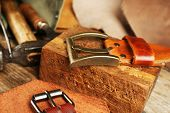 pic of leather tool  - Craft tools with leather belt on table close up - JPG