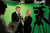 picture of foreground  - Female Presenter Interviewing In Television Studio With Crew In Foreground - JPG