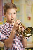 picture of trumpets  - Boy Learning To Play Trumpet In School Music Lesson - JPG